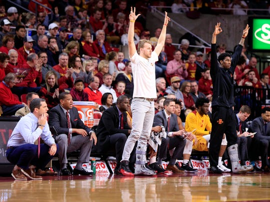 The Iowa State bench cheers a 3-point-shot during a
