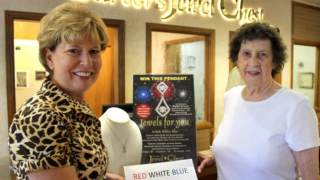 Becky Baker, right, of Mountain Home presents the winning ticket, 132683, for the Red, White & Blue diamond-pendant awarded in a drawing. She is shown with Beth Carter of Carter's Jewel Chest who donated the pendant. Proceeds help support the Red, White & Blue Festival.