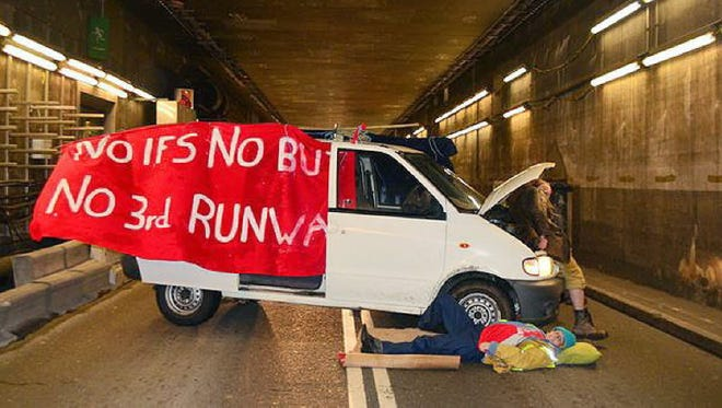 A handout image shows climate change activists blocking an inbound tunnel at Heathrow Airport in London, Nov. 26, 2015. Police arrested five people.