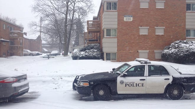 A police car sits outside the Cedar Village Apartments in East Lansing, Mich., where police say two residents were shot Friday night.