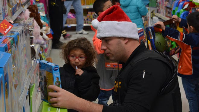 Josh Elford, of the Luna County Sheriff's Office, shopped alongside a student during the Shop with a Cop event held Saturday at Walmart.