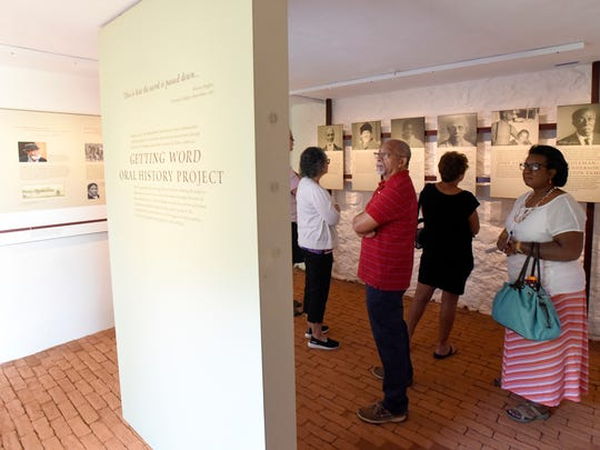 In this photo provided by The Thomas Jefferson Foundation, Bernard Hairston, center, of Charlottesville, Va., looks at an exhibit about Thomas Jefferson's slaves and their descendants during the opening of the South Wing at Monticello, Jefferson's estate in Charlottesville, Va., on Saturday, June 16, 2018.