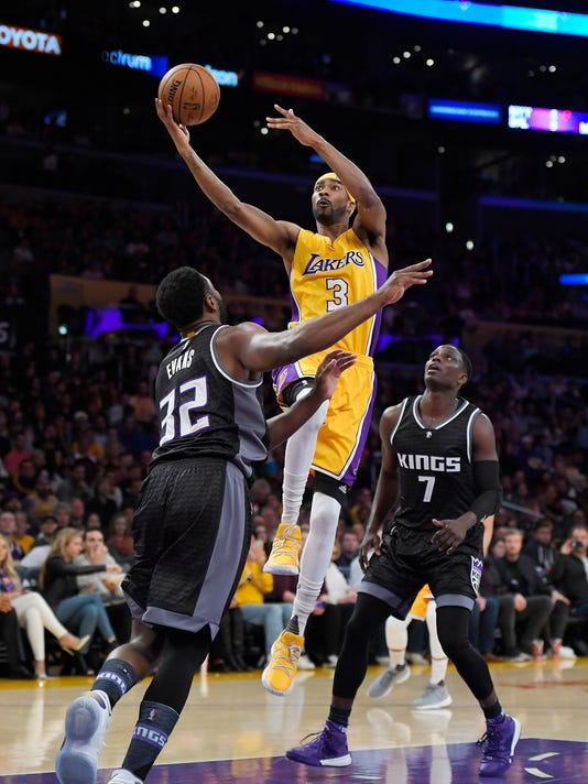 Los Angeles Lakers forward Corey Brewer, center, shoots as Sacramento Kings guard Tyreke Evans, left, and guard Darren Collison defend during the first half of an NBA basketball game, Friday, April 7, 2017, in Los Angeles. (AP Photo/Mark J. Terrill)