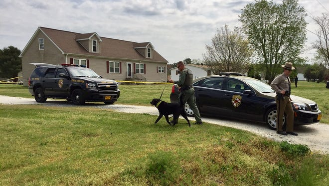 In this April 14, 2017 photo, a Maryland State Police detective walks a police dog to the rear of a Flower Hill Church Road home in Eden where a body of a black man was discovered about 7 a.m., police said.