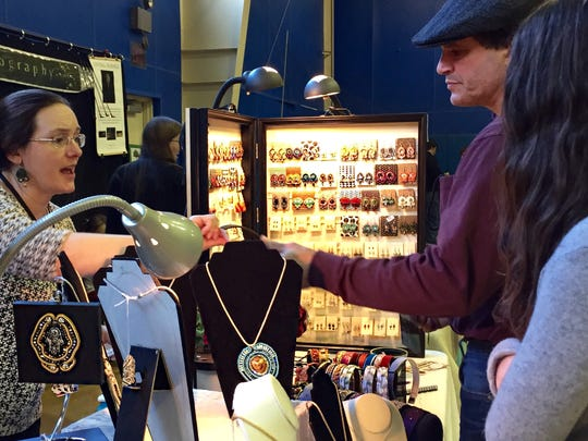 Kelli Peduzzi of Pure Bliss Jewelry and Accessories talks to Poughkeepsie mini Maker Faire attendees John Varriano and his daughter Isabella, 14.