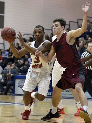 University of Southern Indiana's Bobo Drummond passes to a teammate while being closely guarded by Jimmy King of the University of Indianapolis during the first half of a game.