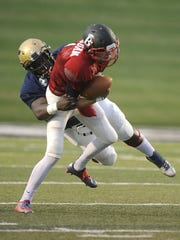 Blue team linebacker Ronnell Wilson (11), from Abilene High, sacks Red team quarterback Jake Morgan (1), from Ballinger, during the third quarter of the Red team's 33-0 win in the FCA Myrle Greathouse All-Star Classic on Saturday, June 11, 2016, at Shotwell Stadium.
