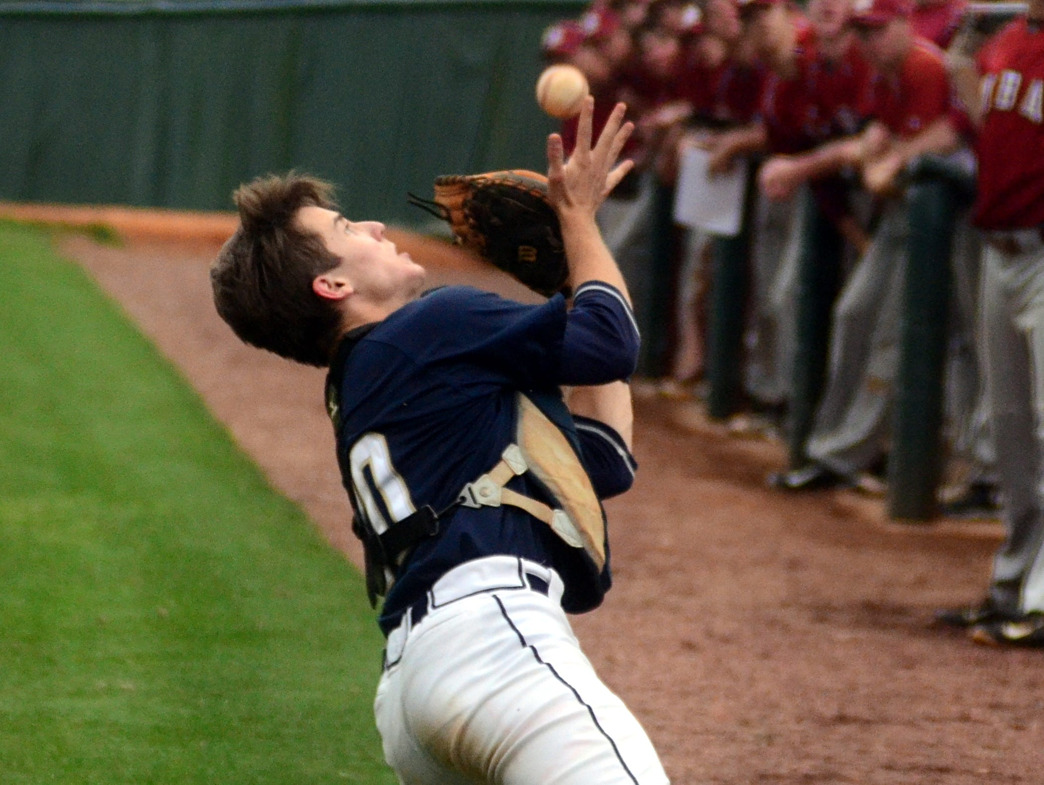 Pope John Paul II High junior catcher Jack Shuttleworth dives to catch a foul ball during third-inning action.