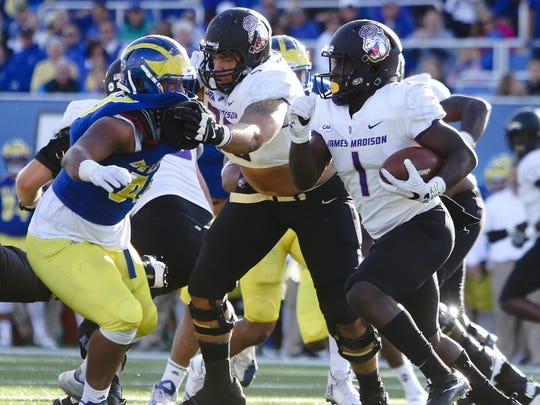 Delaware defensive lineman Cam Kitchen tries to shake off James Madison blocker Aaron Stinnie as he moves for Trai Sharp in the second quarter at Delaware Stadium.