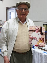 Roland Tess holds a vintage photo of himself with a block of medium aged cheddar with which he won the World Cheese Championship in 1984.
