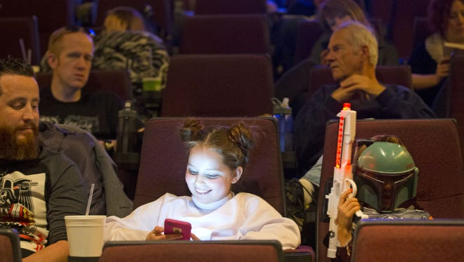 Star Wars fans Jeff Durbin, left and his children, Sailor Durbin, 10, center, and Stellar, 7, right, are seated and ready to see the first showing of Star Wars: The Force Awakens at Harkins Tempe Marketplace on Dec. 16, 2015.