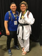 Taylor Ramirez, right, poses with her uncle and coach, Daniel Ramirez, after winning a gold medal at the Amateur Athletic Union National Taekwondo Championships