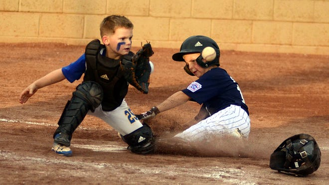 Goodlettsville National 7-8-year-old all-star catcher Braxton Johnson receives a throw at home plate as Clarksville National's Dawson Smith slides in to score during fourth-inning action. Johnson singled twice in Wednesday's 10-9 loss.