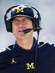 File-This Oct. 14, 2017, file photo shows Michigan head coach Jim Harbaugh walks the sidelines while playing Indiana in the second half of an NCAA college football game in Bloomington, Ind. For a guy who has dealt with so many high-profile people, Jerry Jones, Harbaugh, Pete Carroll to name a few, Jed Hughes manages to stay out of the limelight. That's just fine with Hughes. Brokering deals is what he's all about.  (AP Photo/AJ Mast, File)