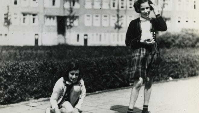 In this May 1941 photo provided by the Anne Frank House Amsterdam, Anne Frank, left, plays with her friend Hanneli Goslar on the Merwedeplein square in Amsterdam. Shortly before Anne Frank and her family went into hiding from the Nazis, she gave away some of her toys to non-Jewish neighborhood girlfriend Toosje Kupers for safekeeping. The toys have now been recovered and Anne's tin of marbles will go on display for the first time this week at an art gallery in Rotterdam, the Anne Frank House Museum says.