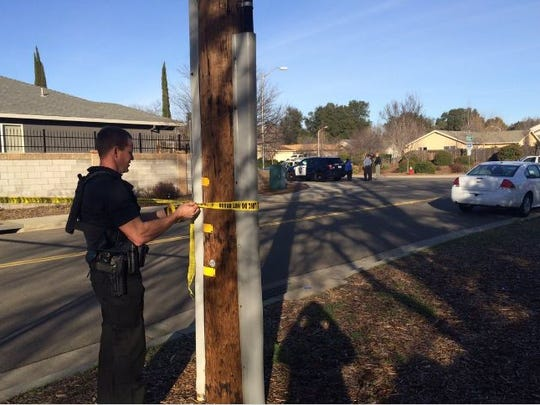 A Redding police officer puts up crime tape to cordon off a neighhorhood near Loma Vista and Churn Creek on Friday as they engage in a standoff.