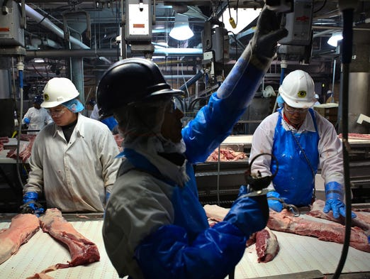 JBS/Swift employees handle meat products as they come down conveyor belts inside the facility Tuesday. Aug. 19, 2014