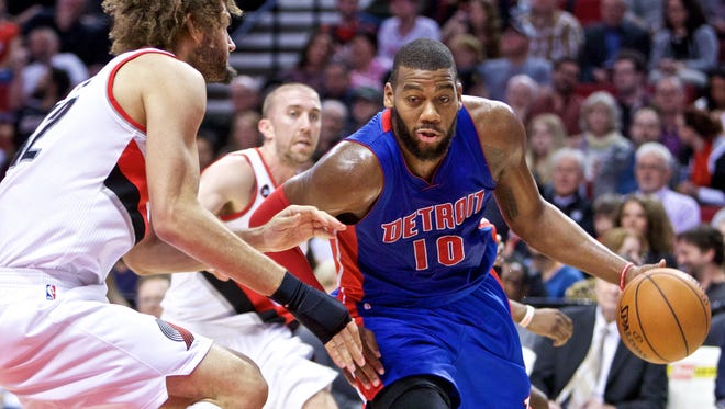 Detroit Pistons forward Greg Monroe, right, drives past Portland Trail Blazers center Robin Lopez on March 13, 2015.