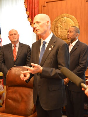 Gov. Rick Scott talks about his $1 billion tax cut plan Wednesday in his Capitol office. With him are Reps. Neil Combee, R-Auburndale, and Darryl Rouson, D-St. Petersburg.
