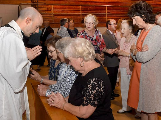Rev. Benjamin James Pitre  bestows a blessing on the faithful following his first Solemn Mass of Thanksgiving Sunday at St. Landry Catholic Church.   he faithful