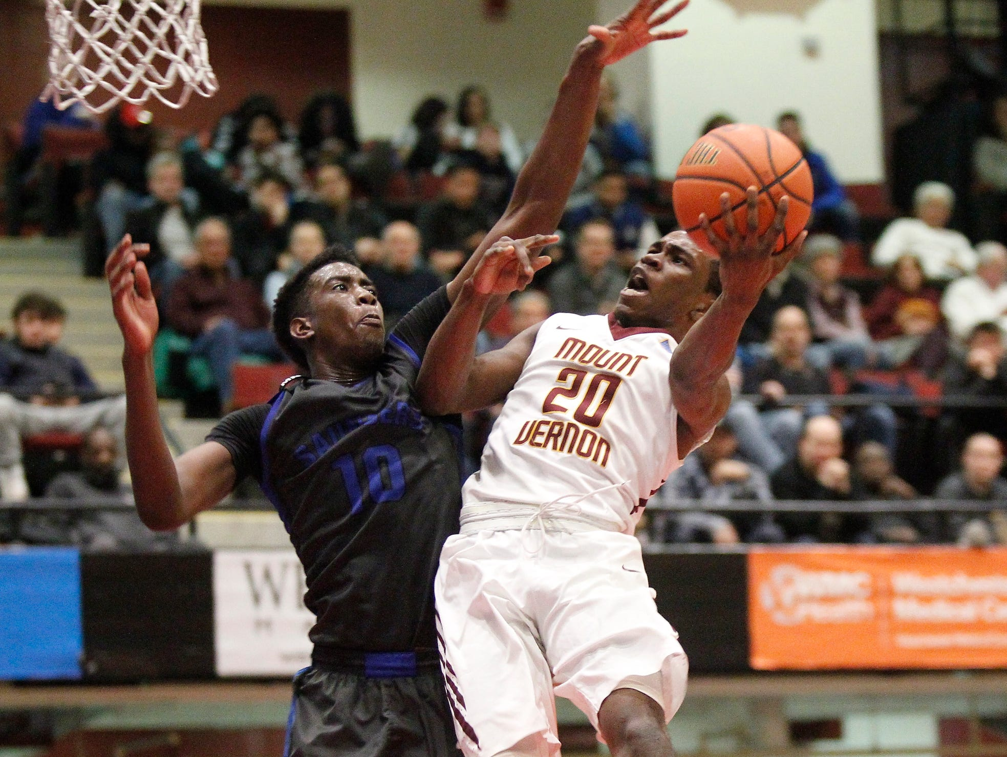 Mount Vernon's Marco Morency (20) puts up a shot as Saunders' Vaughndras Lennon (10) defends during the boys Class AA semi-final basketball game at the County Center in White Plains on Friday, February 26, 2016.