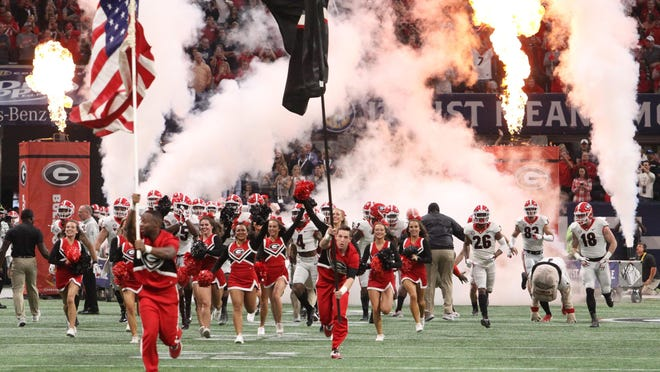 The Georgia football team runs onto the field before the game against Auburn for the SEC championship in Atlanta's Mercedes-Benz Stadium on Dec. 2, 2017.