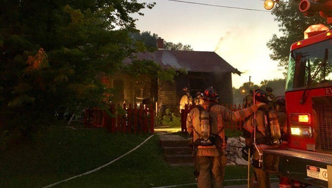 Firefighters work to contain a fire on Evansville's West side Thursday evening.