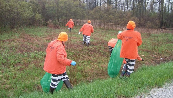 Inmates from the St. Clair County jail help pick up trash at St. Johns Marsh in Clay Township.