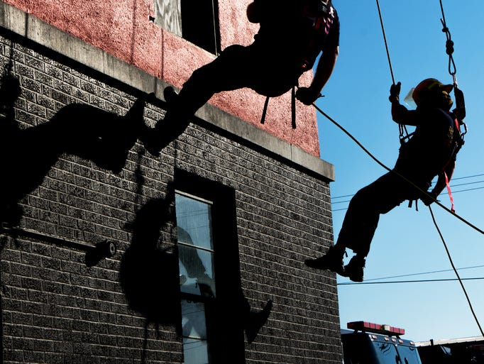 Firefighters rappel down a tower during a Fire Safety