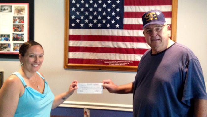 Nikki Iovacchini presents a check from The Delmarva Media Group to Mike Powers of American Legion Post 64.
