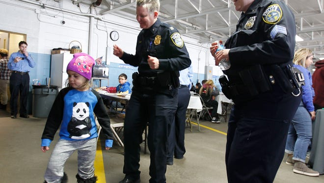 Milwaukee police Capt. Heather Wurth (center) and Sgt. Marissa Gutmann-Gnadt dance with Belitza Fonseca, 5, at the Three Kings Day celebration Saturday at the District 2 police station.
