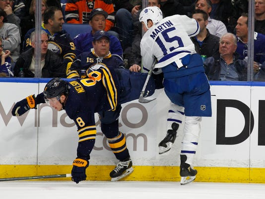 Buffalo Sabres defenseman Casey Nelson (8) and Toronto Maple Leafs forward Matt Martin (15) collide along the boards during the second period of an NHL hockey game, Monday, March 5, 2018, in Buffalo, N.Y. (AP Photo/Jeffrey T. Barnes)