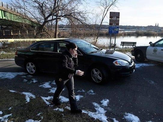 A Syracuse police car drives under the police tape