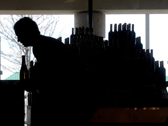 An employee stocks the shelves at the Fine Wine & Good