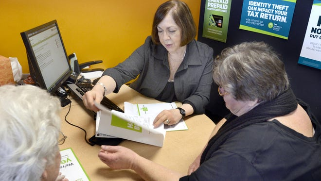 Marsha Anderson, a Senior Tax Adviser 5 with H&R Block, works on taxes for Rosemary Robertson, left, and Robertson's niece, Roxanna Martin, right, on Jan. 16 in Marion, Ind.