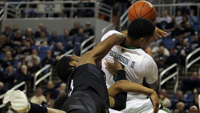 CSU's Fred Richardson is fouled by Nevada's D.J. Fenner during Sunday's game in Reno, Nevada. The Wolf Pack beat the Rams 87-80 in overtime.