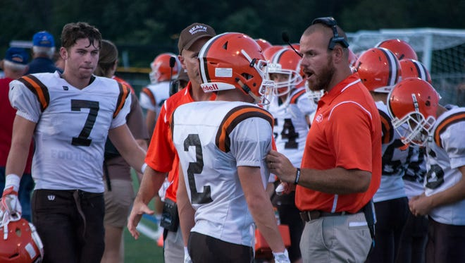 Heath assistant coach Tim Ward talks to Brice Sherburne on the sideline during the Bulldogs' 36-13 win against Licking Valley.