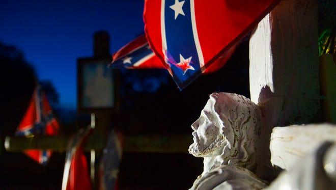 Confederate flags adorn a cross and statue of Jesus Christ at a grave in the Alva Cemetery in Alva, Florida.