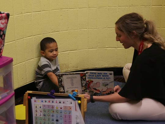 Lindsay Schmitt, a speech therapist for Liberty Post STARS Preschool reads a book to her student Gabriel Foreman. Together, they say the names of the different animals listed in the book.