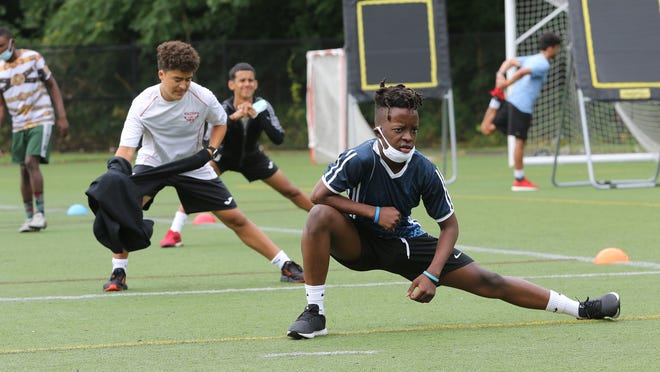 Jonathan Pierre-Louis, 17, stretches out with the other soccer players going through voluntary conditioning drills at Waltham High School, Wednesday morning, July 22, 2020.