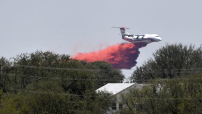 A Texas A&M Forest Service tanker drops fire retardant south of Zephyr Tuesday July 24, 2018.