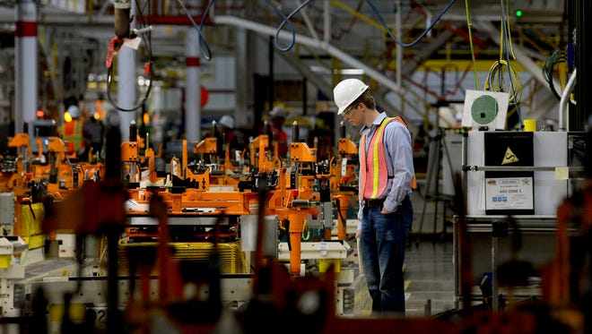 """Patrick Beal, a manufacturing engineering intern, looks at the monitors of the charging unmanned AGVs at the GM Delta Township plant Thursday, June 2, 2016. The plant will re-open Monday after being closed since May for work on a $583-million investment to expand and install new tooling and equipment. The AGVs carry the engine and chassis to the assembly line and help """"marry"""" it to the body."""