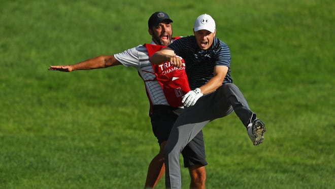 Jordan Spieth celebrates with caddie Michael Greller after chipping in for birdie from a bunker on the 18th green to win the Travelers Championship on Sunday.