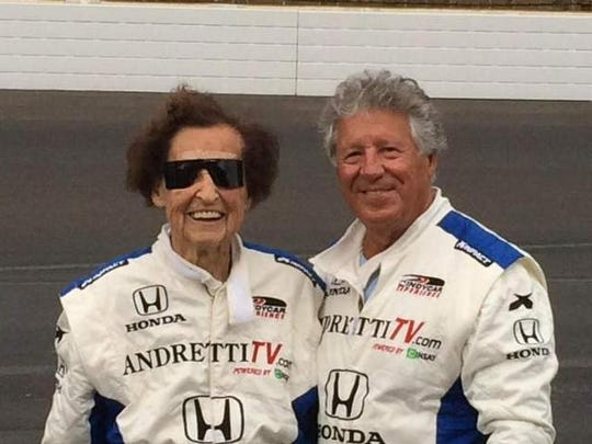 Edith Pittenger poses for a photo with racing legend Mario Andretti, who won the 1969 Indianapolis 500, after taking a couple hot laps around the Speedway with him Tuesday morning.