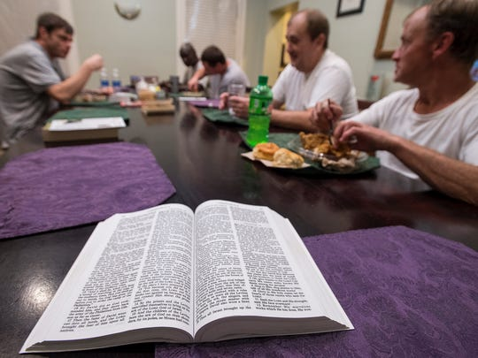 A bible sits on the table as residents eat dinner at