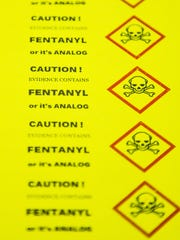 Fentanyl warning stickers lie on a table at the Arizona Department of Public Safety Crime Lab in Phoenix on Sept. 12, 2017.