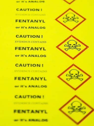 Fentanyl warning stickers lie on a table at the Arizona