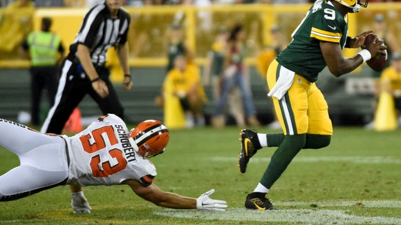 Packers quarterback Marquise Williams (right) scrambles away from Cleveland Browns linebacker Joe Schobert (left) in the third quarter at Lambeau Field on Aug. 12.