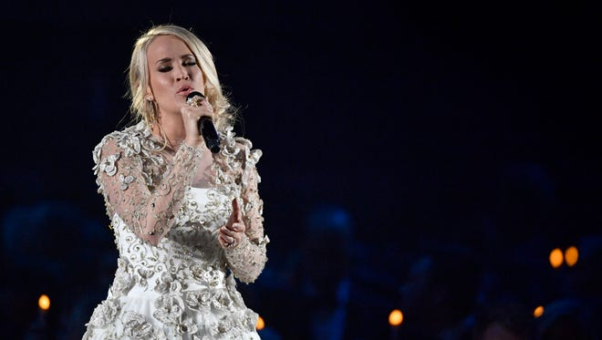 "Carrie Underwood sings ""Softly and Tenderly"" in a tribute to the Las Vegas shooting victims and members of the country community who passed away in the last year during the CMA Awards Wednesday, Nov. 8, 2017 at Bridgestone Arena in Nashville, Tenn."