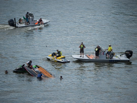 Emergency personnel tend to a capsized boat during